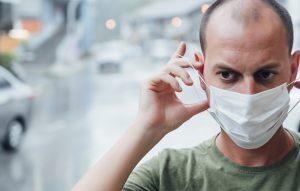 אדם מודאג חובש מסיכה נגד הקורונה