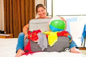 בחורה צעירה אורזת מזוודה לטיול בחול